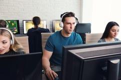 Jovens que jogam jogos de v?deo em computadores Competiam de Esports fotos de stock
