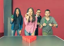 Jovens que jogam o pong da cerveja foto de stock