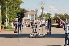 Jovens que montam um Segway e um gyrometer no asfalto no Imagens de Stock