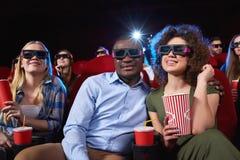 Jovens que olham o filme 3D no teatro de filme Fotografia de Stock Royalty Free