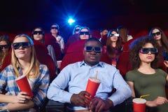 Jovens que olham o filme 3D no teatro de filme Fotos de Stock Royalty Free
