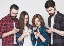 Jovens que olham seus telefones fotos de stock