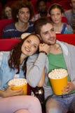 Jovens que olham um filme Fotografia de Stock Royalty Free