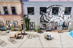 Jovens que ralxing na parte urbana da cidade com galerias artísticas e os bancos estranhos ao redor Fotografia de Stock