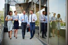Jovens que saem do prédio de escritórios imagens de stock