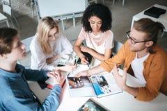 Jovens que sentam-se no escritório que discute algo Grupo de indivíduos frescos que trabalham no projeto novo ao sentar-se no caf imagens de stock