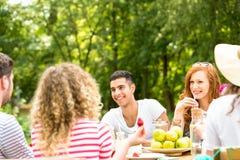 Jovens que sentam-se no jardim e que passam o tempo junto imagem de stock