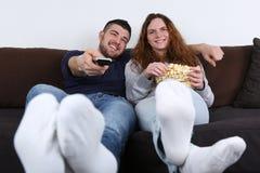 Jovens que têm o divertimento ao olhar a tevê Fotografia de Stock