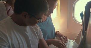 Jovens que trabalham com o portátil no plano video estoque