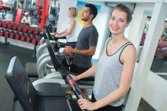 Jovens que treinam em bicicletas de exercício no gym fotografia de stock