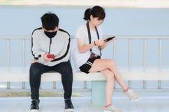 Jovens sérios que usam os smartphones que sentam-se no parque fotografia de stock royalty free