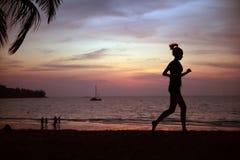 Jovens, senhora apta que faz movimentar-se em uma praia tropical imagem de stock