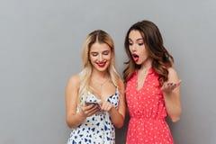 Jovens senhoras chocadas que olham o telefone fotografia de stock