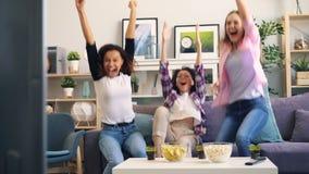 Jovens senhoras que expressam emoções positivas após o jogo bem sucedido dos esportes na tevê video estoque
