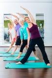 Jovens superiores e que fazem a ginástica no gym imagem de stock