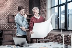 Jovial male engineers estimating blueprint. Team work. Positive energetic two male engineers standing while discussing blueprint and looking at it Stock Photos