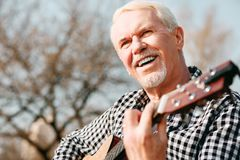 Jovial mature man experimenting with music. Mental health. Low angle of merry mature man laughing and enjoying guitar play royalty free stock images