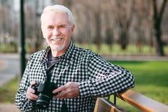 Jovial mature man saving moment Stock Photos