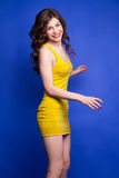 Jovial young model posing in yellow dress on blue background Royalty Free Stock Photos