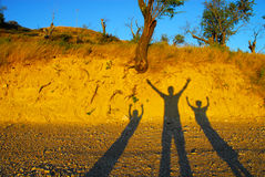 Joy. View of the shadows of three people raising their hands in a concept of joy and hapiness Stock Image