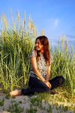 Joy. Young woman sitting on the sand dunes Stock Image
