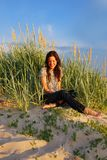 Joy. Young girl sitting on the sand dunes among the grass Stock Images