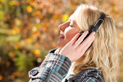 Joy. Young joy woman listening music outdoors in autumn forest Stock Images