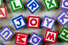 Joy. Wooden blocks forming the word JOY in the center Stock Image