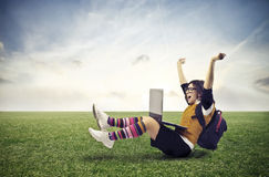 Joy. Girl rejoicing while is using a laptop computer sitting on a large lawn Stock Images