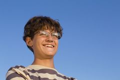 Joy. Smiling teenager on blue sky background Royalty Free Stock Images
