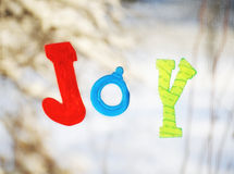 Joy. Jelly letters forming the word Joy off blurred snowy background on a window Royalty Free Stock Images