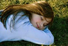 Joy. A girl is enjoying in lying on the grass Stock Photo