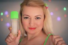 Joy. Blond happy woman holding bottle of perfume stock photo