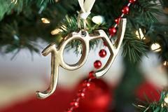Joy Christmas Ornament. Gold joy Christmas ornament hanging on tree Royalty Free Stock Photography