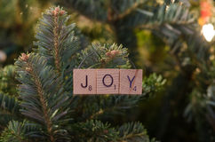 Joy Christmas Ornament. The letter joy is spelled out with lettered wooden tiles to create a homemade and festive Christmas ornament royalty free stock images