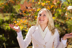 Joy fall. Happy young woman catching falling tree leaves in autumn forest Royalty Free Stock Image