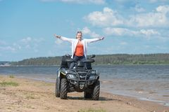 Joy of freedom. Young beautiful girl rejoices to freedom on ATV near the river Stock Photo