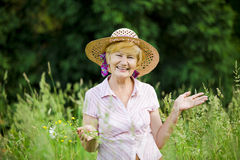 Joy. Friendly Happy Mature Woman in Straw Hut with Stretched Arms. Smiling Old Lady in Straw Cup with Stretched Arms in Meadow Stock Photo