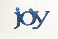Joy. Glitter covered ornament with joy white background stock photo