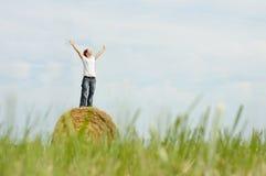 Joy, grassland, woman. Woman on hay bale in autumnal grassland enjoying a warm windy day stock image