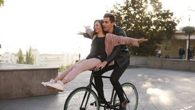 Joy and happiness of young couple have fun riding on the same bike in outdoor activity with sun backlight on the