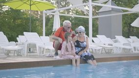 Joy happy grandmother, grandfather and little granddaughter having a rest by the luxury pool. Joy happy grandmother, grandfather and little granddaughter having stock video footage