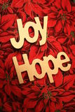 Joy and Hope. Gold Joy and Hope wood pieces on a red poinsettia fabric Royalty Free Stock Image