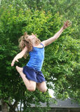 Joy of Jumping. Beautiful young girl jumping in the air in front of a tree Royalty Free Stock Photography