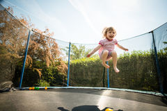 Joy - jumping trampoline. Little child enjoys jumping on trampoline - outside in backyard royalty free stock image