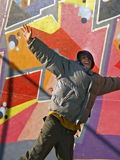 Joy of life. Teen boy jumping with big smile on his face, graffiti at the background Royalty Free Stock Image