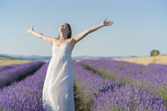 The joy of life. Beautiful young woman wearing a white dress celebrating the beauty of life standing in the middle of a lavender field in bloom Royalty Free Stock Photos