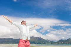 Joy of life and freedom on the beach. Joy of life and freedom expressed by a young man on the beach, standing with hands in the air Royalty Free Stock Photo