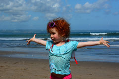 Joy of the little girl on the beach of wide ocean Royalty Free Stock Photos