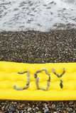 Joy message from pebbles on a air-bed. Stock Photo